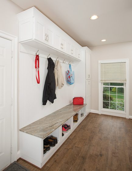 The renovated mudroom area boasts a built-in unit of cubbies and hooks.