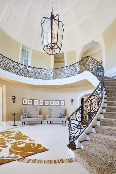 The foyer boasts a 28-foot domed ceiling and an intricate iron stair rail.