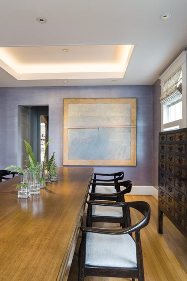 An abstract canvas pops against a dining-room wall embellished with a lavender glaze.