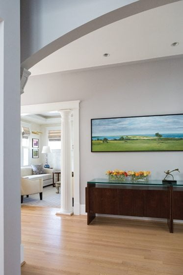 In the entry hall, a painting depicts the view from the owners' weekend beach retreat.