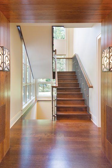 The staircase is embellished with forged-steel balusters.