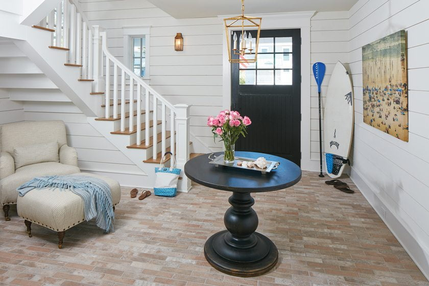 The wide stair's bespoke design exposes staggered steps and a whitewashed-brick floor.