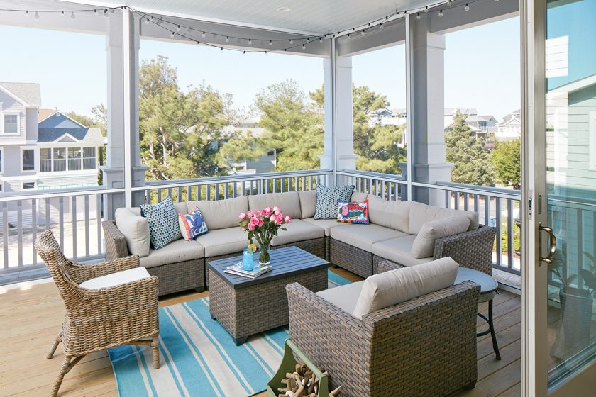 A summery Dash & Albert rug grounds the screened porch's comfortable seating area.