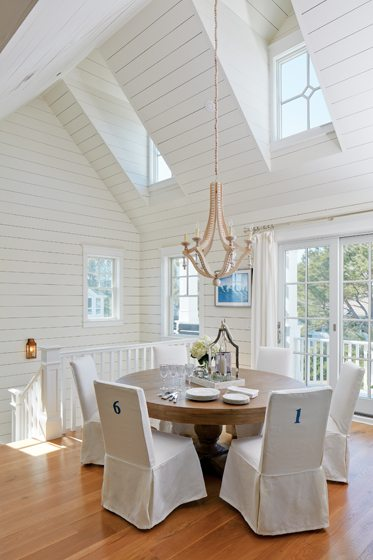A casually elegant chandelier from Interior HomeScapes hovers over the dining table.