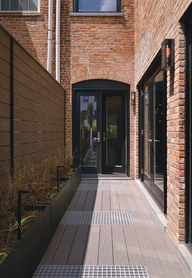 The outdoor walkway features custom privacy screens.