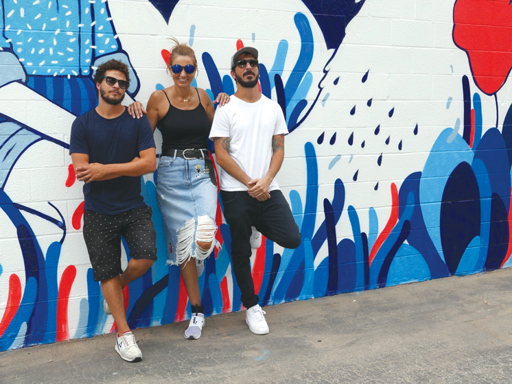 Urban Walls Brazil creator Roberta Pardo poses between Brazilian artists Mateus Bailon and Mateu Velasco.