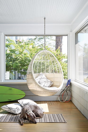A whimsical cb2 pod hanging chair suspends from the ceiling on the screened porch.