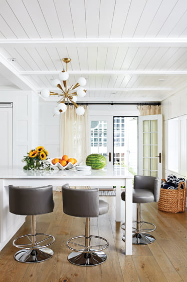 In the renovated kitchen, the capacious island creates table space below a vintage light fixture.