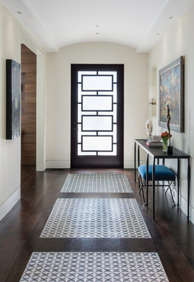 Sachs designed colorful inlaid mosaics that mimic rugs in the entry hall.