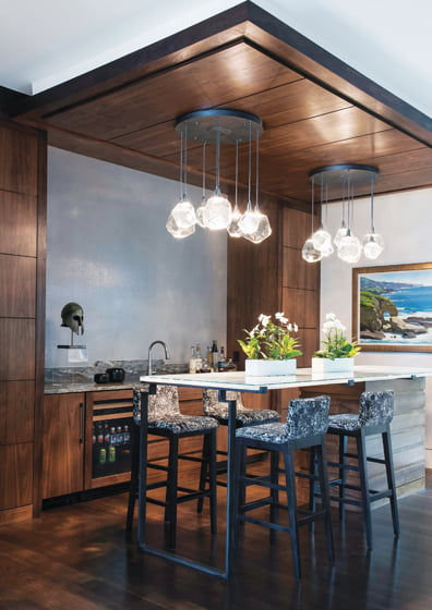 Centered around a custom steel-and-glass table, the family-room bar area is a party magnet.