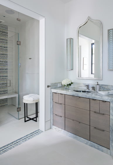 The master bath balances masculine and feminine elements, with a wood vanity and delicate mosaics.