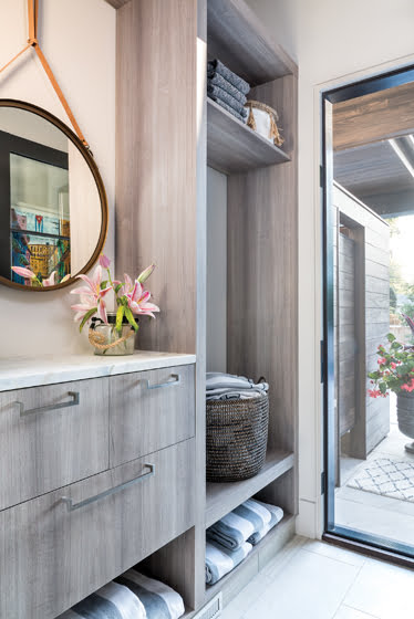 Also connected to the pool terrace, a powder room boasts custom cabinetry and tile.