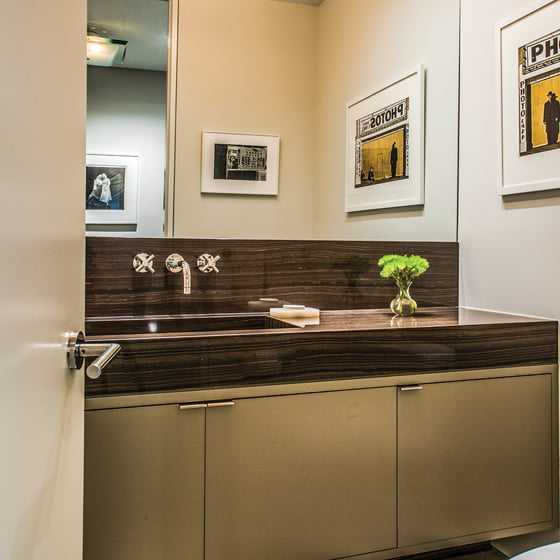 In the powder room, the sink is integrated into the vein-cut Eramosa marble countertop.