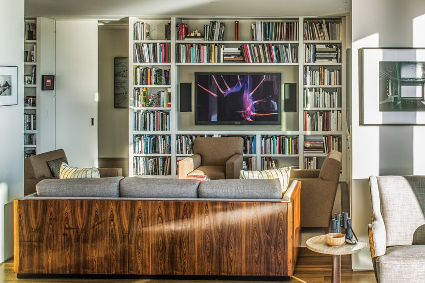 A TV lounge area with built-in shelving now occupies the original library space.