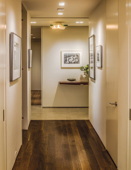 The hallway leading to the living area is a gallery for the owner's collection of photographs.