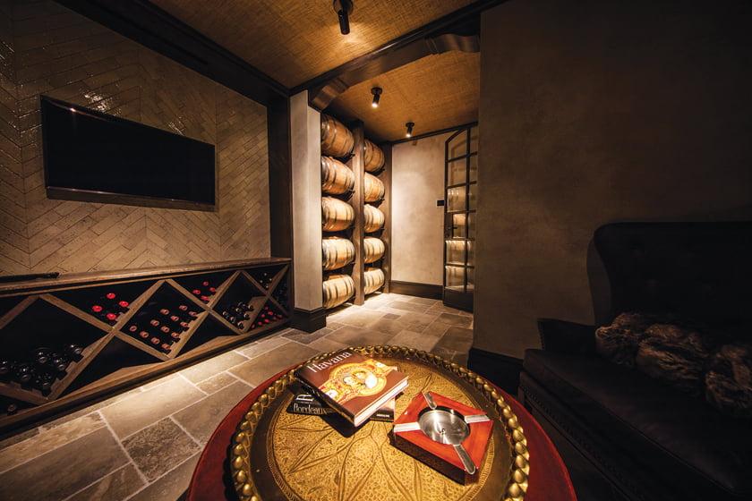 The whiskey/wine cellar houses custom barrel racks of Sutton's design.