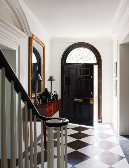 In the entry hall, new detailing and a rejuvenated stair rail establish a classical note.