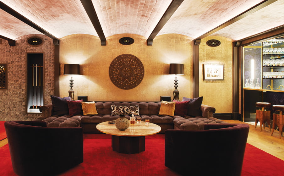A bronze wall covering and jewel-toned décor conjure a speakeasy in the lounge.