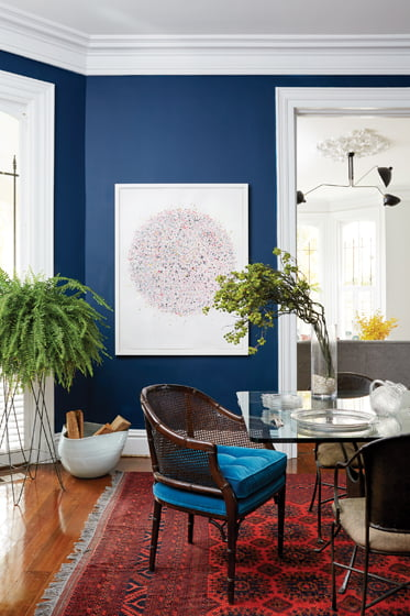 In the dining room, deep blue walls are a vivid backdrop for art by Amy Goodwin.