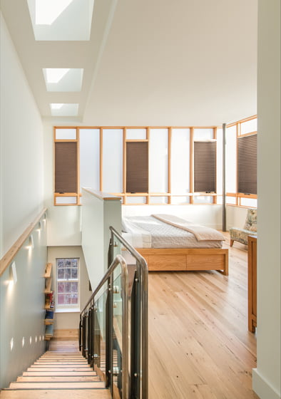 The stairs lead to the new master bedroom, a modern take on the traditional sleeping porch.