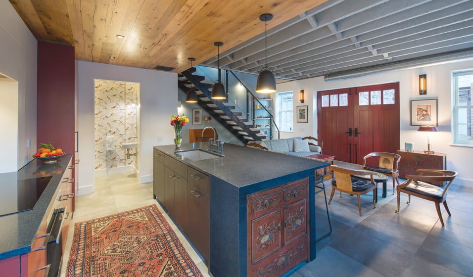 Exposed beams, welded-steel stairs and carriage doors bring an industrial edge to the open living space.
