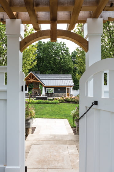 A gated entry to the backyard frames the pool house. © Angie Seckinger