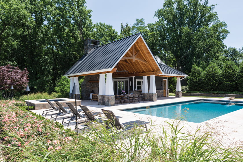 The pool house includes a catering kitchen and an outdoor entertainment area with a fireplace. © Angie Seckinger