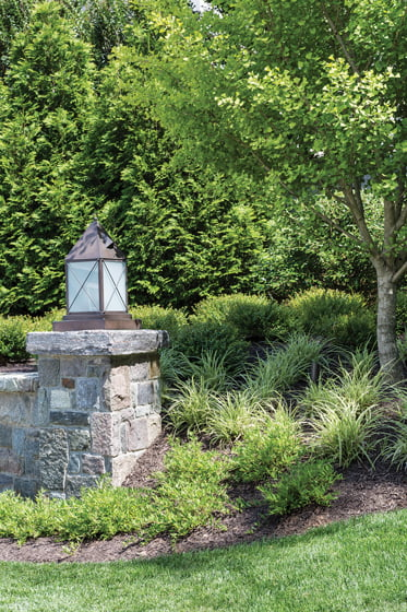 A stone wall marks the entry to the home. © Angie Seckinger