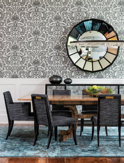 In the dining room, a custom mirror and sideboard by McLain Weisand blend with wallpaper by Cole and Son.