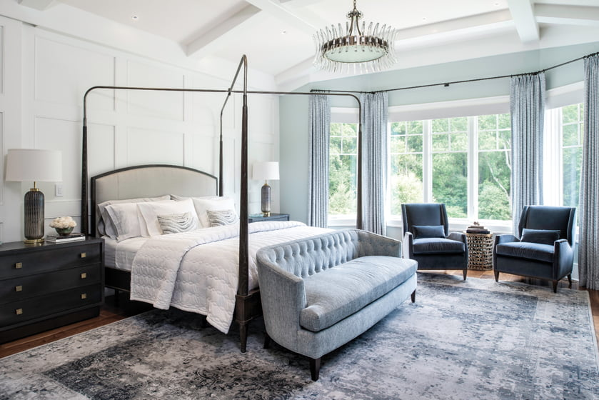 A four-poster bed by Vanguard matches the scale of the vaulted master bedroom.