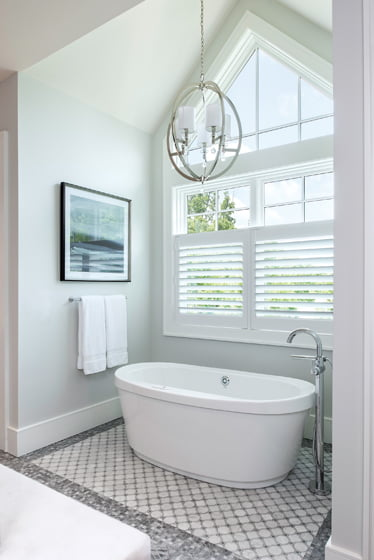 A pendant by Metropolitan Lighting hangs over a Ferguson tub.