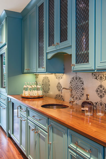 The teal pantry houses multiple cold-storage units and drawers for beverages.