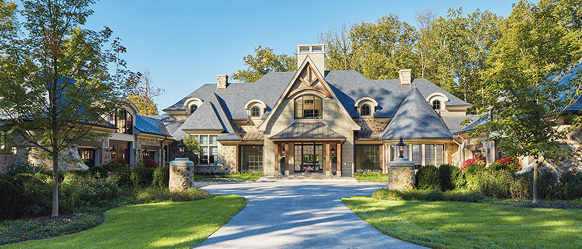 A long drive culminates in a forecourt with his-and-her garages to either side of a stately entry.