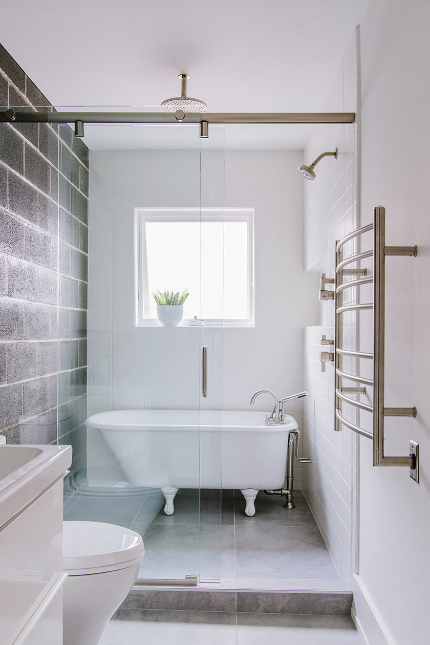 The bathroom is clad in concrete-look porcelain tile and features a restored claw-foot tub.