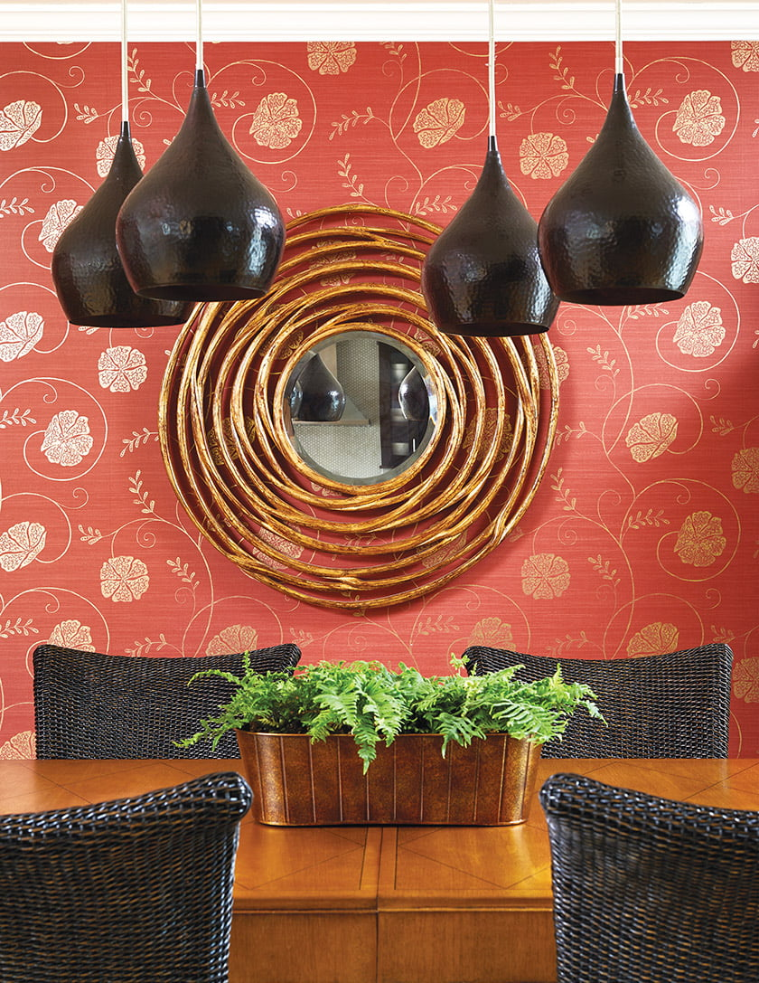 The dining room boasts deep-red Zoffany wallpaper with a gold flower motif and eclectic furniture in warm wood tones.
