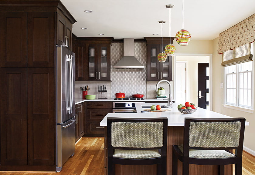 """In the remodeled kitchen, Lee Industries stools pull up to the island; its L shape """"keeps the kitchen area contained,"""" says Houck."""
