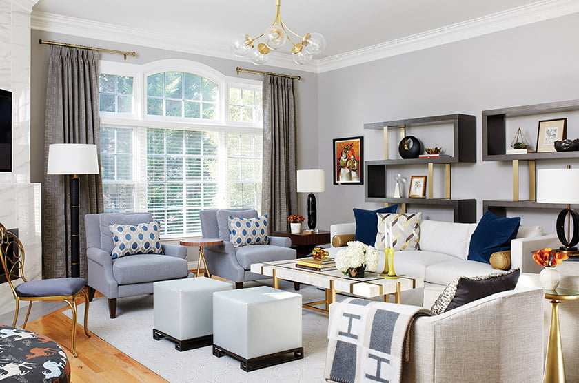 The family room features a Barbara Barry sofa with a stone-and-brass coffee table and club chairs by Mr. & Mrs. Howard.