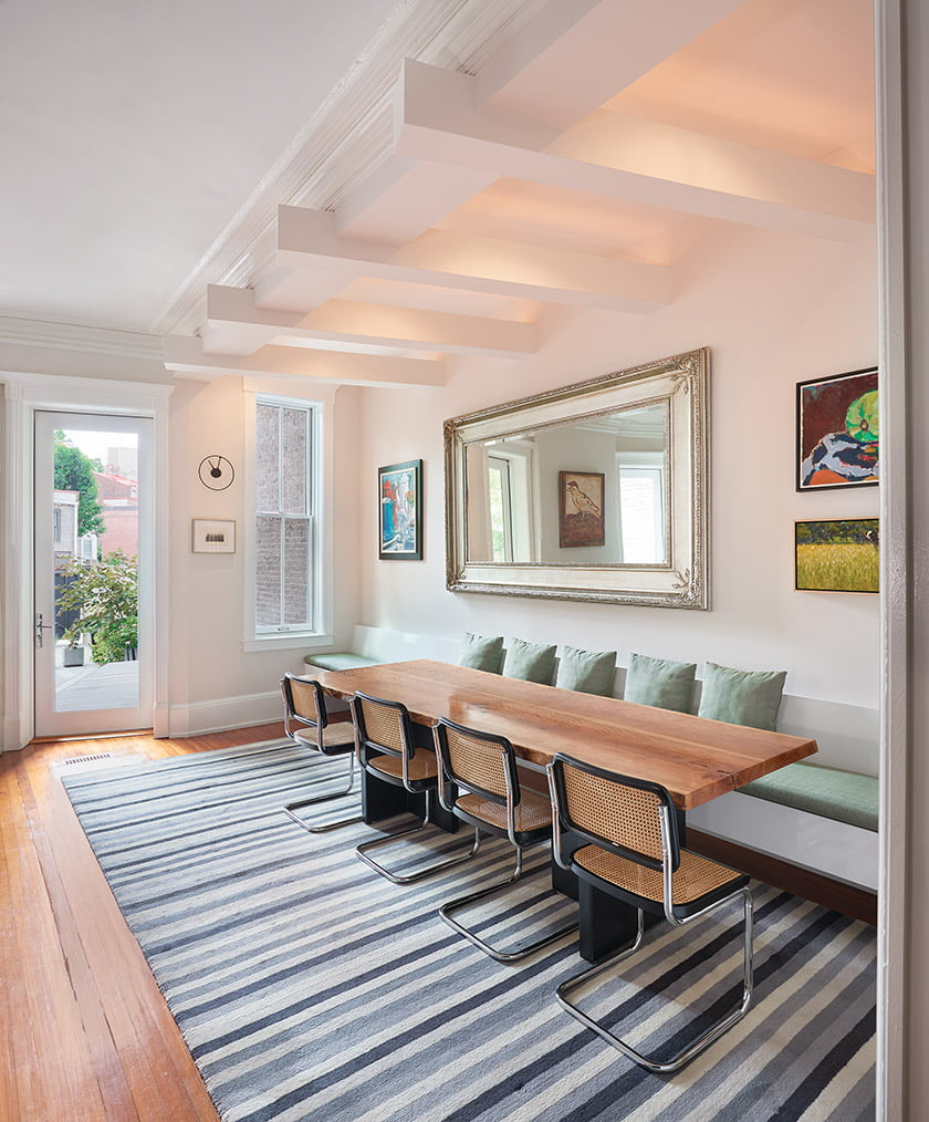 Above the kitchen table, a sculptural ceiling treatment preserves the room's original moldings.