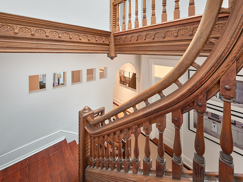 A view from the stairs down to the second floor reveals cutouts in the wall that bring light into the husband's office.