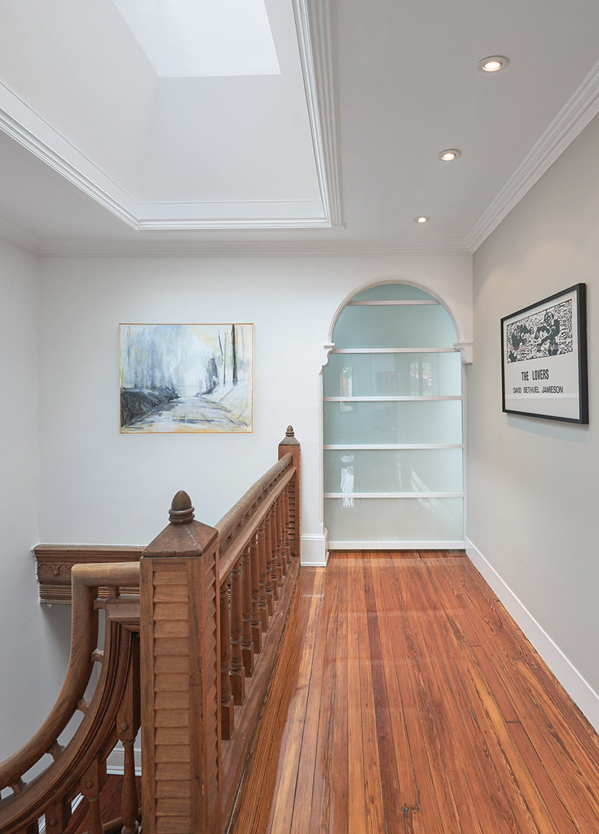 The third floor houses the master suite behind a frosted-glass door.