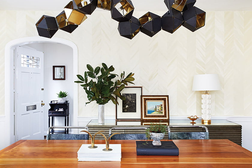 A dramatic light fixture by Gabriel Scott crowns the dining room.