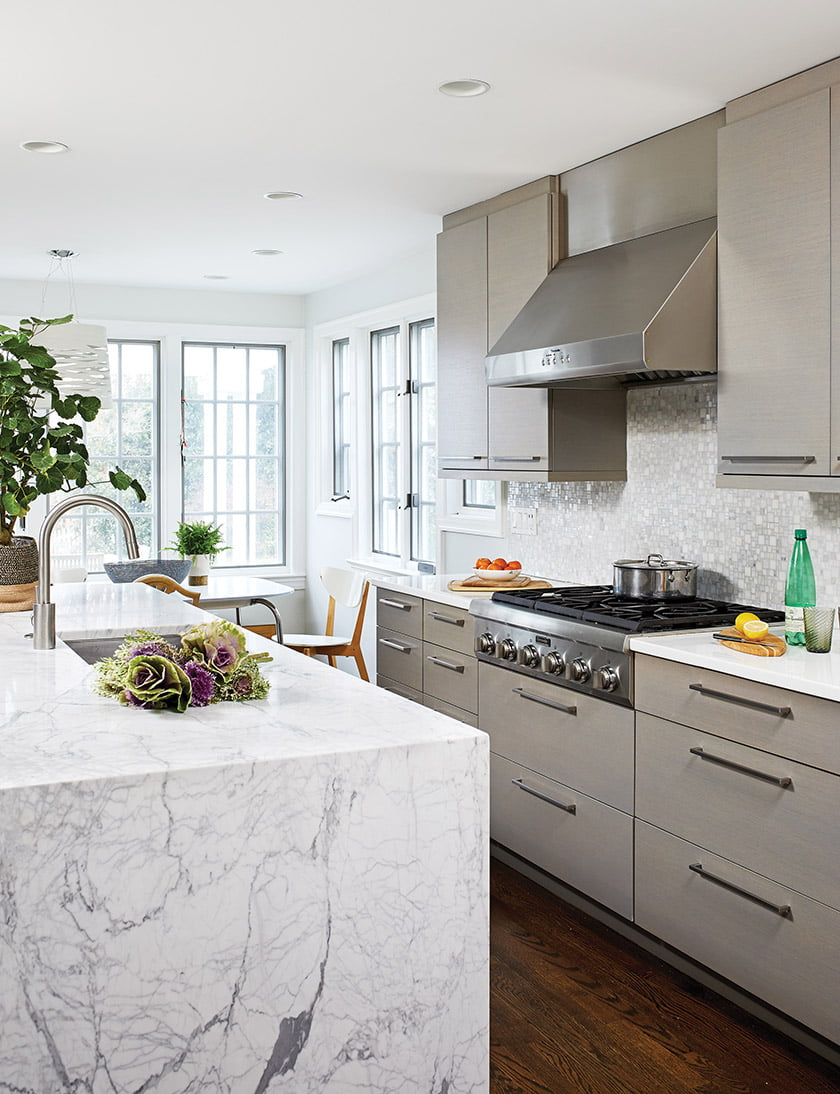 The kitchen was remodeled by Gilday Renovations using gray-painted cabinetry and a marble-topped island.
