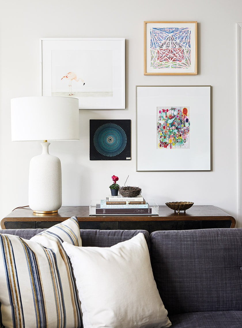 Behind the sofa, a Visual Comfort lamp and eclectic art complement a console by Julian Chichester.