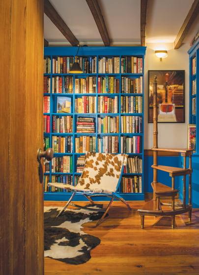 Dutch Carpentry LLC custom-built floor-to-ceiling bookshelves to match the existing one in cobalt blue.