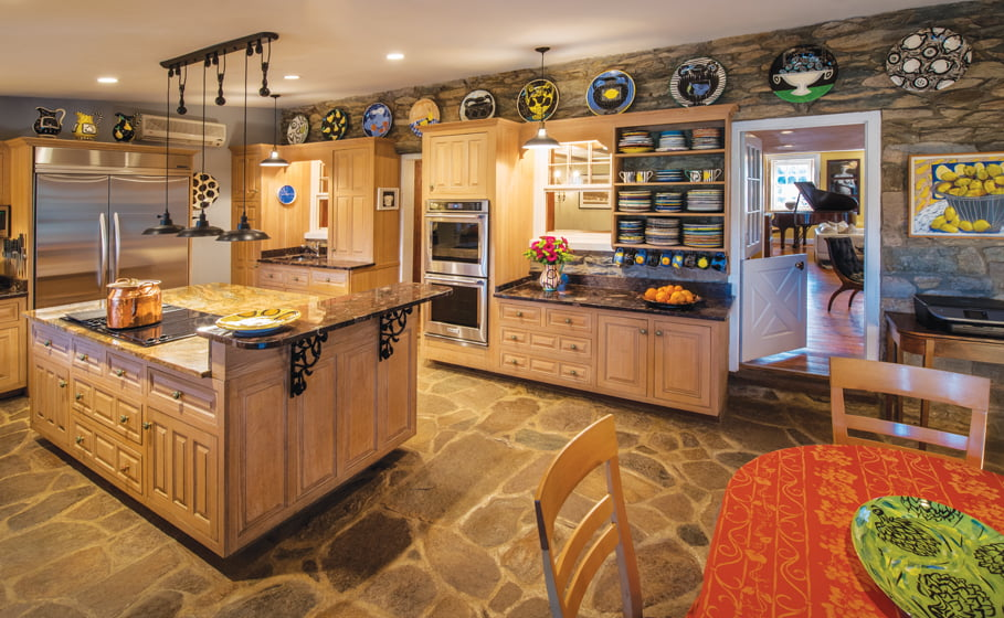 Originally an exterior space, the kitchen encloses a stone floor that continues onto the adjacent patio.