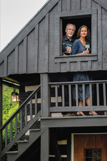 The proprietors are framed in a window of their log cabin, one of six century-old structures on the property.