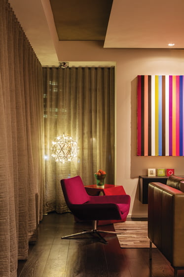 Fuchsia chairs from B&B Italia and an oil painting by Gian Garofalo add color to the living area.