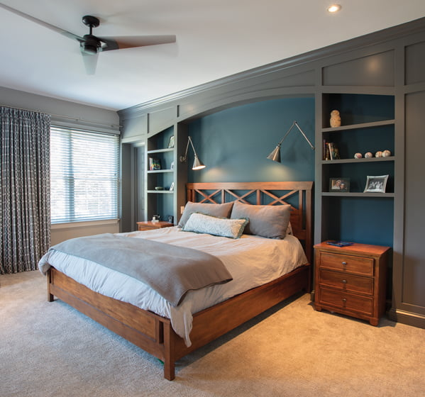 A wall of built-ins frames the bed in the master bedroom.
