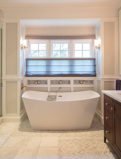 Marble and millwork impart refinement to the master bath.