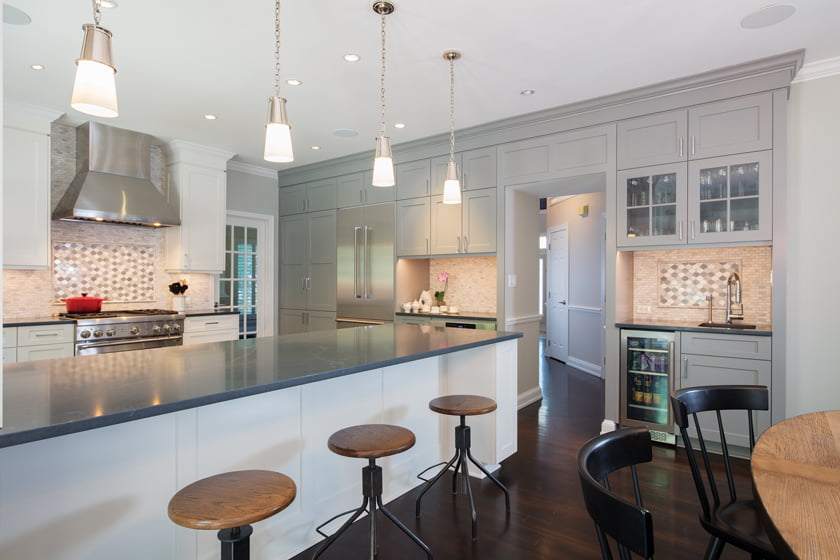 The kitchen features Woodharbor cabinetry, Silestone counters and a marble mosaic backsplash.